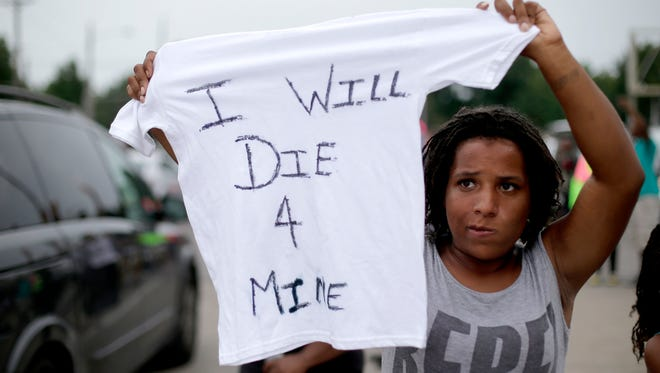 Chelsea Johnson of St. Louis on Friday protests the shooting death of Michael Brown by police nearly a week ago in Ferguson, Mo.