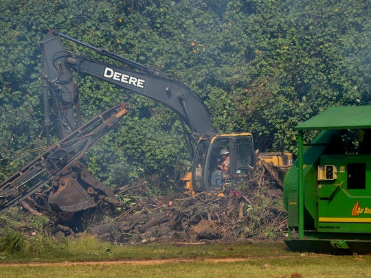 A Pacific Unlimited Inc. worker uses an excavator to move green waste in Hagåtña on Dec. 26, 2017.