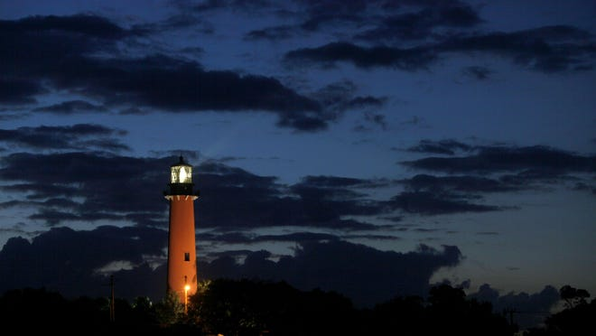 The eastern sky brightens behind the Jupiter Inlet Lighthouse before dawn.