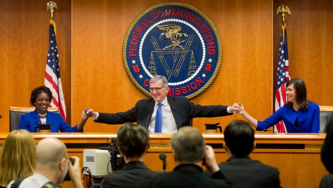 """Federal Communication Commission (FCC) ChairmanTom Wheeler, center, joins hands with FCC Commissioners Mignon Clyburn, left, and Jessica Rosenworcel, before the start of their open hearing in Washington, Thursday, Feb. 26, 2015. Internet service providers like Comcast, Verizon, AT&T, Sprint and T-Mobile would have to act in the """"public interest"""" when providing a mobile connection to your home or phone, under new rules being considered by the Federal Communications Commission. The rules would put the Internet in the same regulatory camp as the telephone, banning providers from """"unjust or unreasonable"""" business practices."""