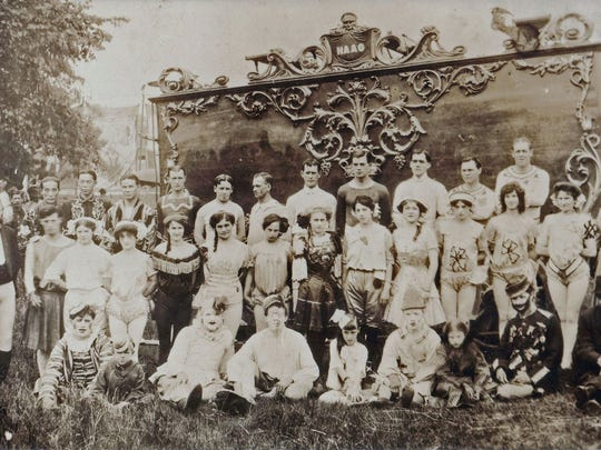 Mighty Haag Shows performers and crew pose before one of the rail cars during the early 20th century.