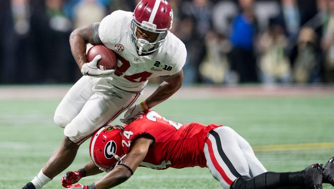 Alabama running back Damien Harris (34) is upended by Georgia strong safety Dominick Sanders (24) in first half action of the College Football Playoff National Championship Game in the Mercedes Benz Stadium in Atlanta, Ga., on Monday January 8, 2018. (Mickey Welsh / Montgomery Advertiser)