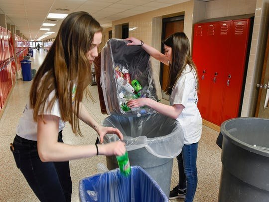 Rocori Environmentalist Club members Tessa Stukey and Brooke Froehle collect recycling placed outside classrooms after school Friday, April 13, in Cold Spring.
