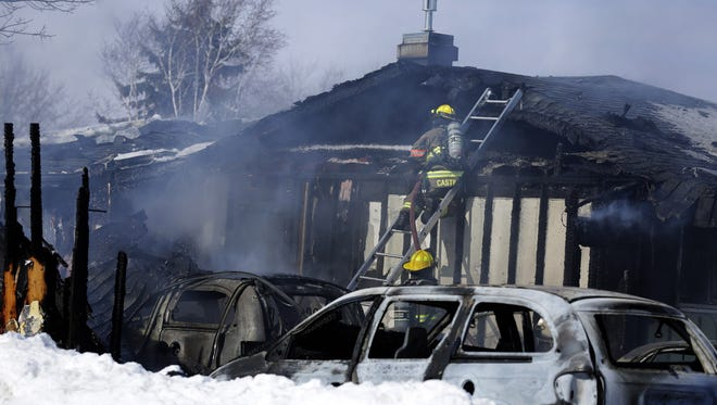 Firefighters battle a fire at 206 Welhouse Drive in Kimberly, Wis., Sunday, February 7, 2016.