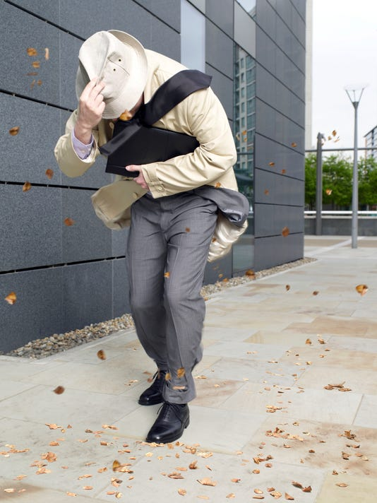 Businessman holding onto hat walking in windy weather