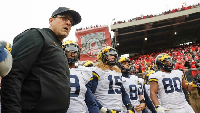 Michigan coach Jim Harbaugh leads his team onto the field to face undefeated Wisconsin on Saturday, Nov. 18, 2017 in Madison, Wis.