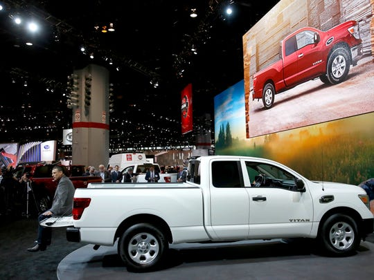 Fred Diaz, left, division vice president and general manager North American trucks and light commercial vehicles, Nissan North America, sits on the tailgate of a 2017 Nissan Titan King Cab truck as he talks about the sales performance of the Titan during the media preview of the Chicago Auto Show, Thursday, Feb. 9, 2017, in Chicago.