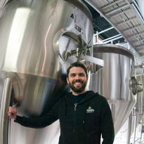 Grant Pauly, founder and brewmaster of 3 Sheeps Brewing Co., stands by one of his brewing kettles at the company's 14th Street location inside Hops Haven.