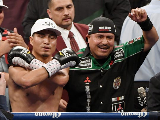 Mikey Garcia, left, and his brother and trainer Robert Garcia celebrate after Mikey knocked out Dejan Zlaticanin in the third round of their WBC lightweight title fight.
