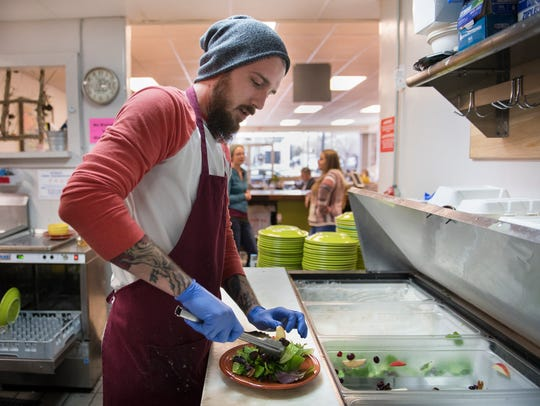 Chef Austin Brown prepares a salad with apples, cranberries,