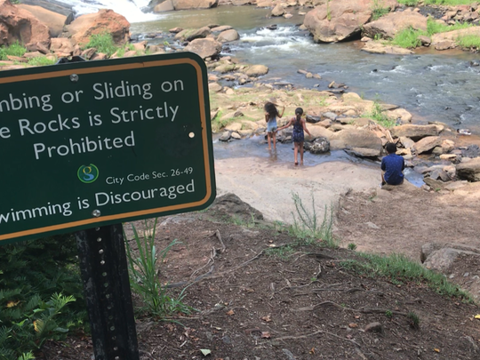 Kids splash around in a pool of the Reedy River, below a sign warning against swimming.