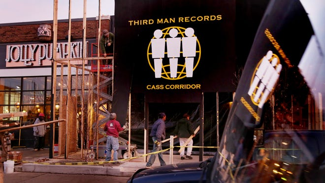 Workers dismantle a plywood facade in front of the soon-to-open Third Man Records store on Canfield in Detroit on Wednesday, Nov. 25, 2015.