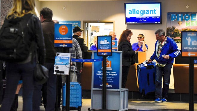 Passengers check in for an Allegiant flight to Florida in this file photo.