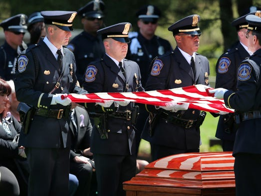 IMPD police officers fold the flag that was draped on the casket of IMPD Officer Kimberlee Carmack during the burial services at Crown Hill Cemetery on Wednesday, April 23, 2014.