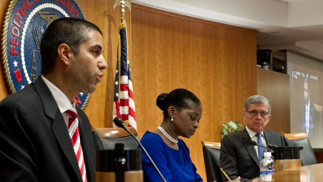 FCC Commissioner Ajit Paj speaks as Commissioner Mignon Clyburn(C) and FCC Chairman Tom Wheeler(R) look on during a meeting of the commissioners May 15, 2014 at the FCC in Washington, DC. The commissioners voted today on a proposal for protecting an open Internet. After allowing a couple of months for public comments and replies, the commission will try to draw up final rules that satisfy a majority of commissioners.