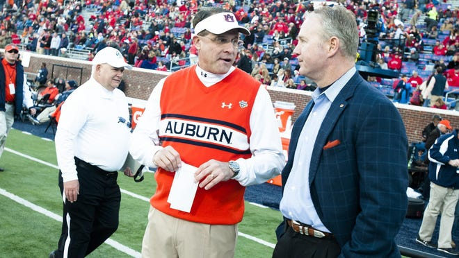 Auburn head coach Gus Malzahn talks with Jay Jacobs, Auburn athletic director, before the NCAA football at University of Mississippi in Oxford, Miss., on Saturday, Nov. 1, 2014.