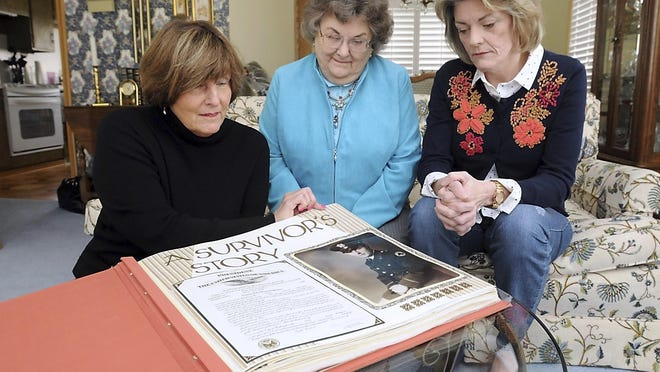 Vivian (Schramski) Borak and her daughters, Mary Brose and Terry Krause, page through a scrapbook filled with memorabilia from her husband's life in World War II and as a POW in the Philippines.
