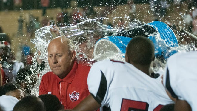 Central-Phenix City head coach Jamey DuBose has a cooler of water dumped on him after the Red Devils beat Prattville in 2014, his first year at the school.