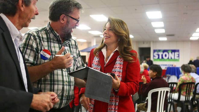 Linda Evans looks over election results with Johnny Hildreth and Doug Hassett, left, at the East Valley Republican Women Federated headquarters Tuesday in La Quinta.
