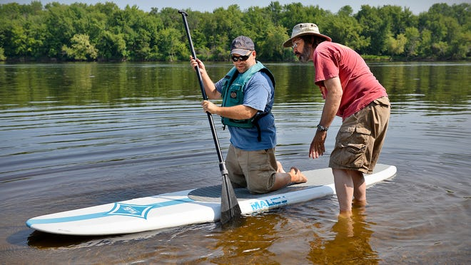Bill Ness (right) of Clear Waters Outfitting gives Steven Mick, St. Cloud, a quick lesson for his first time on a paddleboard Saturday during the Take a Day Off on the Mississippi event.