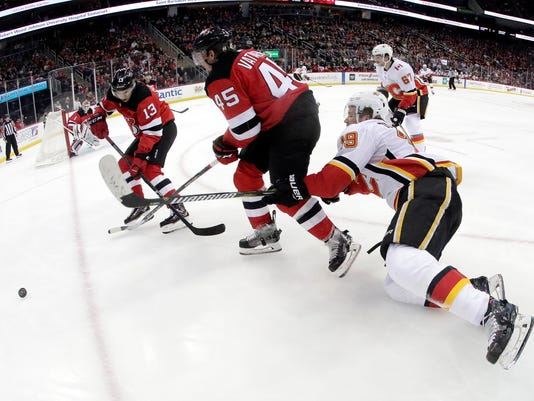 Calgary Flames left wing Matthew Tkachuk (19) loses his balance while compete for the puck with New Jersey Devils center Nico Hischier (13), of Switzerland, and defenseman Sami Vatanen (45), of Finland, during the first period of an NHL hockey game, Thursday, Feb. 8, 2018, in Newark, N.J. (AP Photo/Julio Cortez)