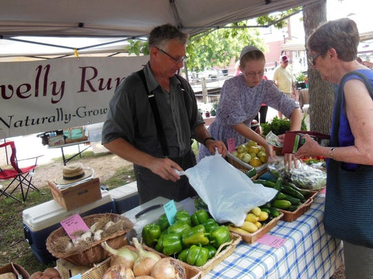 Scott Miller tends the Gravelly Run Farm stand at the Riverwalk Farmers Market in downtown Milford. He sells typical fare, alongside oddities like lemon cucumber and ground cherries.