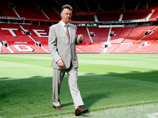 Manchester United's Louis van Gaal walks off the pitch following a photocall for his new player Angel di Maria, at Man. Utd's Old Trafford Stadium in Manchester, England, Thursday, Aug. 28, 2014. Manchester United have signed winger Angel Di Maria from Real Madrid for a British record transfer fee of £59.7 m. The Argentine winger had a medical in Manchester on Tuesday and has signed a five-year deal. Di Maria is likely to make his debut on Saturday against Burnley in the Premier League. (AP Photo/Alastair Grant)