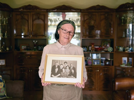Claudia Liberchuk holds a framed photograph taken on