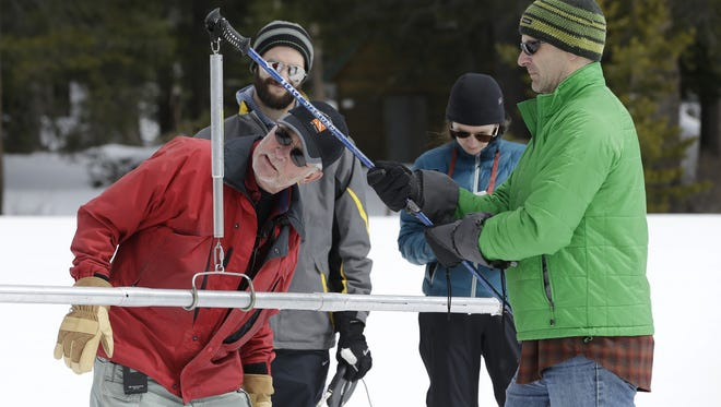 Frank Gehrke checks the weight of the snow pack on a scale held by Dan Brumbaugh, right, as he performs the snow survey at Phillips Station in Echo Summit on March 30.