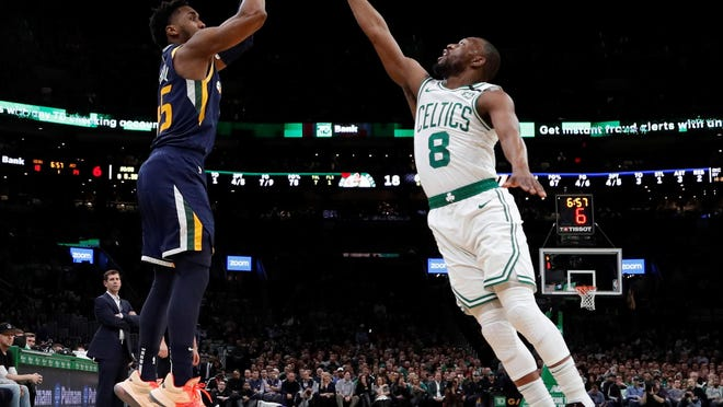 Undoubtedly suffering from a sore knee during this game in early March, Celtics guard Kemba Walker leaps in an attempt to block the shot of the Utah Jazz's Donovan Mitchell at TD Garden.