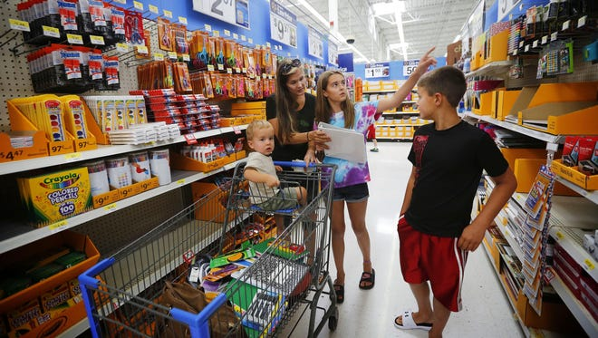 Cynthia Olson of Ankeny shops for school supplies with her children, Ella, 11, Avry, 9, and Bennett, 1, on Tuesday at Wal-Mart in Ankeny. Retailers are expecting big crowds for the state's tax-free holiday Friday and Saturday.