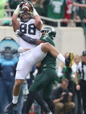 Michigan Wolverines TE Jake Butt makes a catch against Michigan State Spartans CB Darian Hicks during the third quarter Saturday, Oct. 29, 2016 at Spartan Stadium in East Lansing.