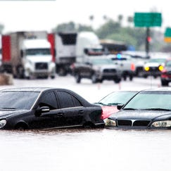 Traffic is stopped in the eastbound lanes of I-10 and cars are underwater at 43rd Ave. and I-10 in Phoenix, Monday morning after record-setting rainfall caused massive flooding throughout the Valley.  More than 20 cars were stranded when fast rising water flooded the underpass.      flood