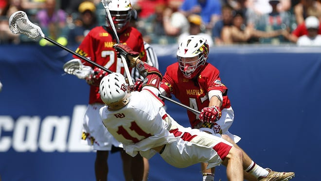 Maryland's Mac Pons (43) checks Denver's Jack Bobzien (11) during the first half of the NCAA Division I men's lacrosse championship, Saturday, May 25, 2015, Philadelphia. (AP Photo/Rich Schultz)