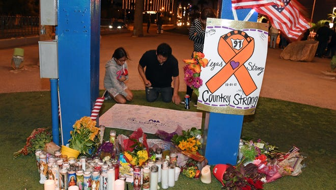 People sign a poster at a makeshift memorial at the base of the Welcome to Fabulous Las Vegas sign in memory of the victims of Sunday night's shooting, on Oct. 3, 2017 in Las Vegas.
