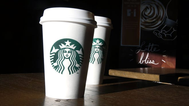 In this this Friday, Jan. 17, 2014, file photo, Starbucks cups are shown mugs in a cafe in North Andover, Mass.