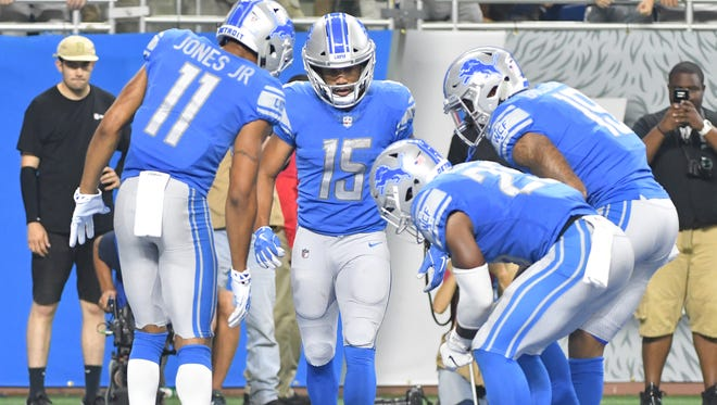 Lions' Golden Tate celebrates his touchdown with a quick game of curling in the third quarter.