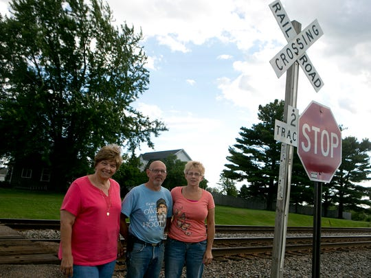 From left, neighbors Linda Weinfurter, Jay and Lori Butts pose next to the train tracks where they say Canadian National trains block off access to the main road in Auburndale.