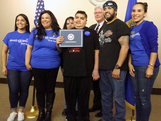 Gabriel, center, holds his U.S. Marshals certificate with his parents, Make-A-Wish North Texas employees and David Sligh, acting U.S Marshall for the Western District of Texas.
