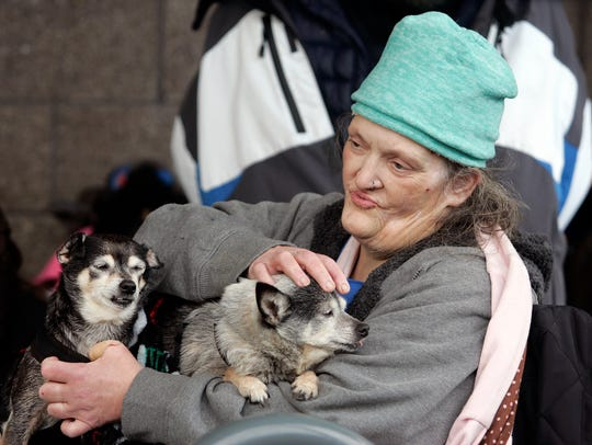 Tazha Zeira, with her dogs Sadie and Sophie, took shelter under an outdoor awning during Wednesday night's storm.