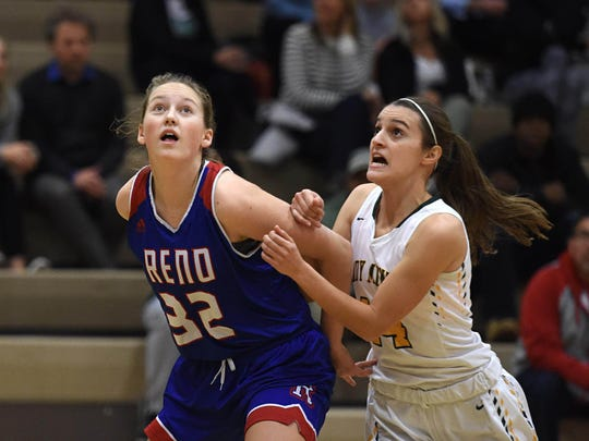 Reno's Gracen McGwire, left, and Manogue's Hannah Reviglio look for a rebound during at Bishop Manogue on Dec. 12, 2017.