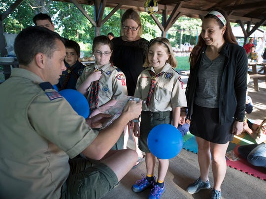 From the left, Steve Owens pulls badges for excited Scouts Angela Trantham, while her mother, Jennifer, looks on, and Stella Millek, while her mother, Christy, watches during an end-of-year celebration at Lake Redman.