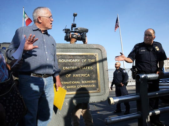 Ruben Garcia, director of Annunciation House talks to a U.S. Customs and Border Protection official on behalf of a woman and her son from Guatemala who has been trying to seek asylum in the U.S. on the summit of the Paso Del Norte International Port of Entry Friday.