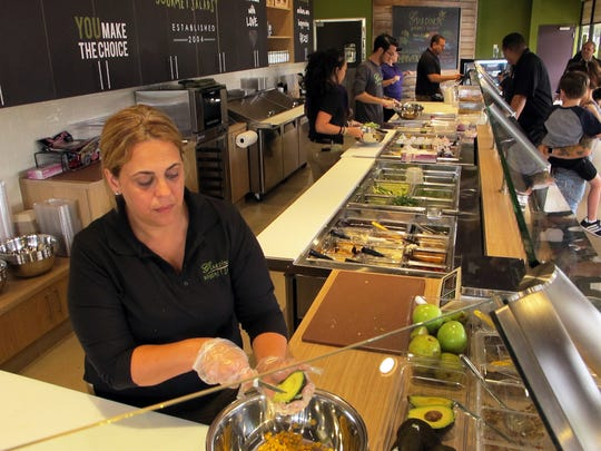 Company co-founder Ody Lugo, left, helps serve customers Monday during the opening day of Giardino Gourmet Salads, 3370 Pine Ridge Road, in Naples.