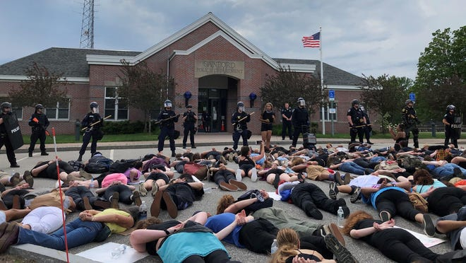 Hundreds marched to the Sanford Police Department headquarters on Saturday, where about two dozen officers stood silently with shields and weapons. The demonstrators lay on the ground in a manner reminiscent of the way George Floyd died in Minneapolis.