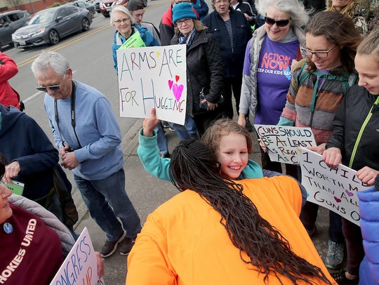 "Scarlett Olson, 8, of Bremerton, gets a hug as "" March For Our Lives "" participants smile. The second grade student was one of the youngest to march in Silverdale Saturday."