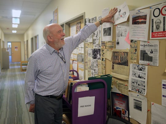 Olympic College history professor Phil Schaffer, who is retiring after 50 years at the college, examines some of the years' worth of clippings in the hallway outside of his office.