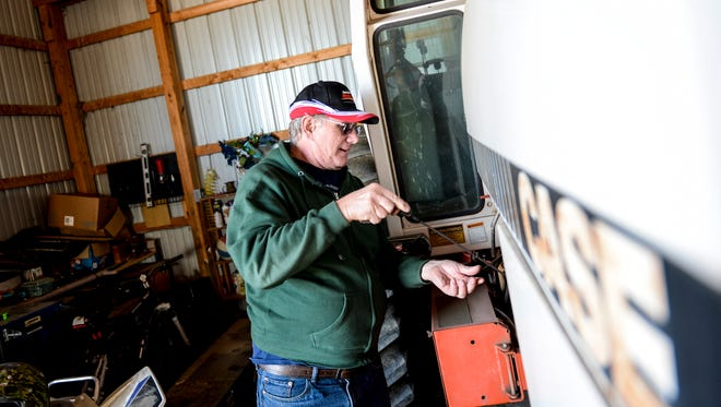 Lynn Struphar checks the oil in his tractor on his farm along Route 934 in North Annville Township on Friday November 20, 2015. Struphar works his family farm that was started in 1882 and is one of 16 century farms in Lebanon County.