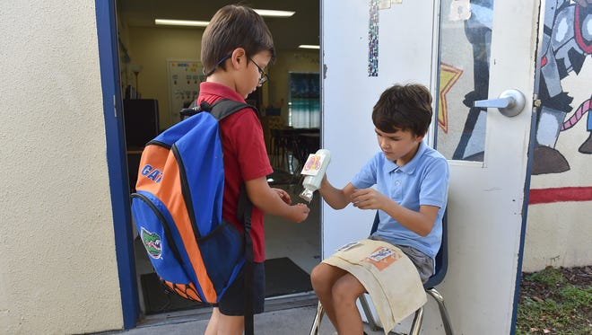 Timothy Powell (left) gets a greeting and some concentration cream (hand lotion) from Landon Quinlin before walking into their second-grade classroom Tuesday, Nov. 14, 2017, at Indian River Academy. Courtney Antosh's second-grade class has included several types of teaching methods to help children learn and behave as part of the Moonshot Moment and Learning Alliance programs.