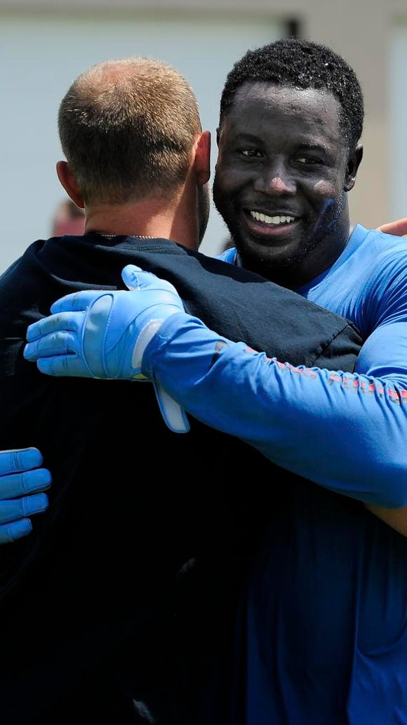 Linebacker Moise Fokou, right, hugs Tim Shaw after the the Titans took the ALS Ice Bucket Challenge in Shaw's honor.